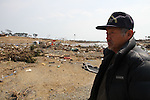 """March 29, 2011, Minamisanriku, Miyagi, Japan - More than two weeks after the tsunami the rural area between Kesennuma and Minamisanriku lies in ruin. Terao Saito, 62, looks across the wreckage at where his factory used to be. """"The JSDF troops are working really hard. I know they are."""" (Photo by Wesley Cheek/AFLO) [3682]."""