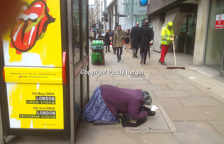 Woman kneeling in Moorgate in the City of London and holding a white plastic cup to collect donations in. Rolling Stones poster.<br />