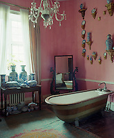 A collection of blue and white Chinese porcelain jars and vases are displayed in this pink bathroom