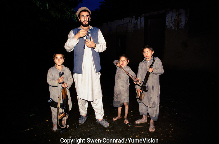 Nuristani commander with his three sons, next to a opium field in East Afghanistan..