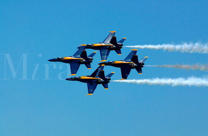 The Blue Angels FA 18s fly in diamond formation with trails of white smoke against a clear blue sky