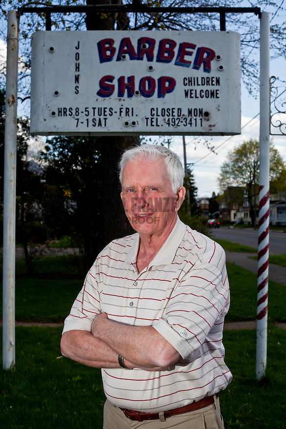 John Murray stands in front of his barbershop located at 4403 S. Salina St.