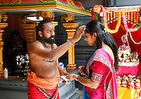 Nederland Den Helder  2016  06 26. Jaarlijkse tempelfeest bij de Hindoe tempel in Den Helder.. Vereniging Sri Varatharaja Selvavinayagar voltooide in 2003 het gebouw dat wordt gebruikt voor het bevorderen van kunst en cultuur. Een ander deel wordt gebruikt voor het praktiseren van religieuze waarden. Het hoogtepunt van de feestperiode is het voorttrekken van de wagen ( chithira theer of ratham ). Dit is een kleurrijke optocht, waarbij de godheid Ganesh in de wagen wordt voortgetrokken door gelovigen. Bij een jonge vrouw wordt een stip op het voorhoofd gezet door een priester.  Foto Berlinda van Dam /  Hollandse Hoogte