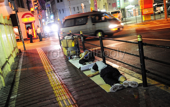Unemployed and homeless men sleep on the roadside in central Osaka, Japan.