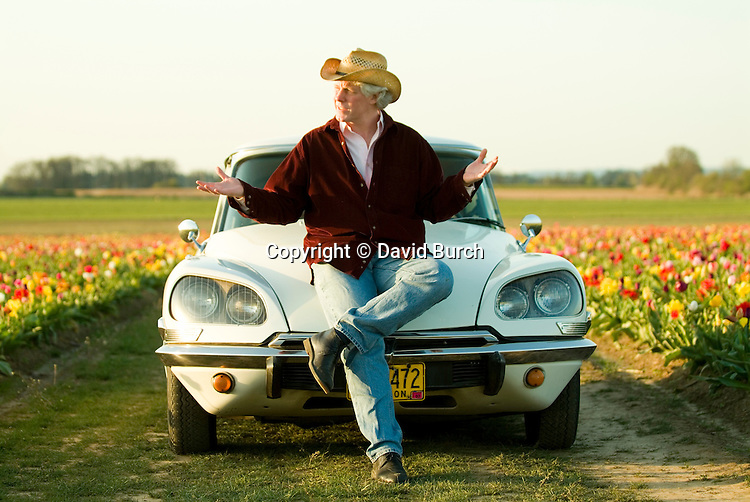 Mature man sitting on car, looking away