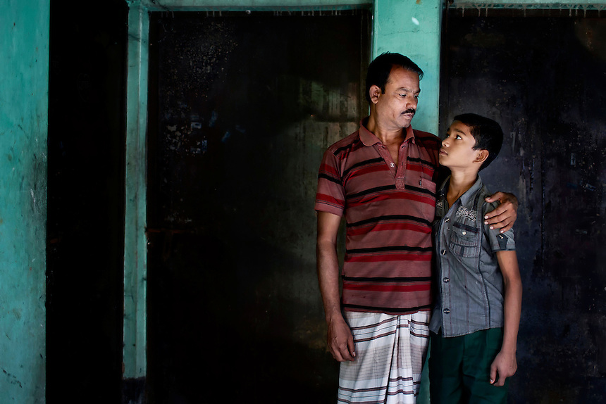 Mozammel Haque, left, looks to his son Abu Rayhan, posing for a portrait in front of the burnt living room in which his wife, Yanur Begum (32), was killed when a factory fire ravaged Tazreen Fashions in Ashulia, Bangladesh.