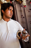"Sanjay Kumar, 22, a former snake charmer, holds his snake charming musical instruments, that he now uses in cultural performances (without the snakes), at his home in Naraina gaon, Titana village, Samalkha town, Haryana, India on 15th June 2012. ""Only during elections does the government pay attention to us,"" he says. India's snake charmer communities suffer from a loss of livelihood because of stringent wildlife laws and are forced to resort to begging or working as daily wage labourers. A new program to encourage the snake charmer's children to attend school is underway, to keep them from becoming daily-wage child labourers or joining their parents in scavenging and begging in cities. Photo by Suzanne Lee for The National"