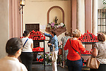 People lighting red candles in the courtyard of the church of San Antonio Abad, Seville, Spain