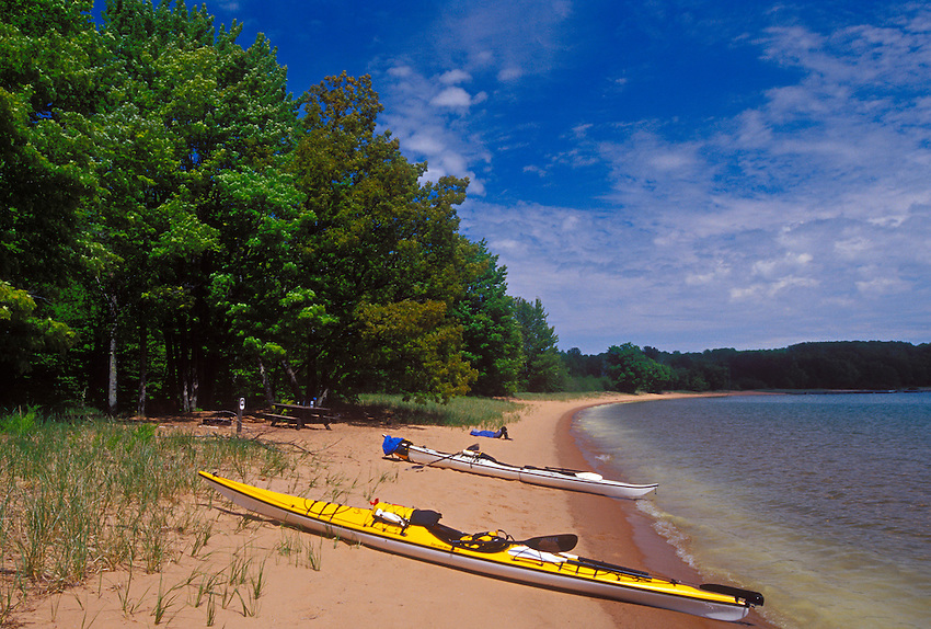 Kayaks and a paddler rest on a sand beach on Stockton Island in the Apostle Islands National Lakeshore near Bayfield, Wis.