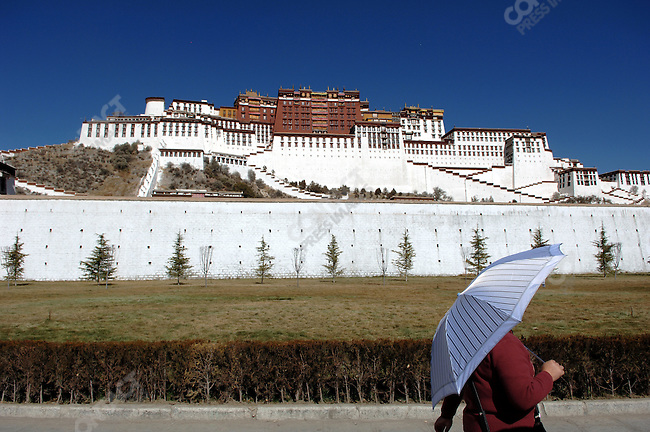 A Chinese tourist, parasol in hand, passed on her way to the entrance of the Potola Palace in Lhasa, Tibet. November 14, 2006