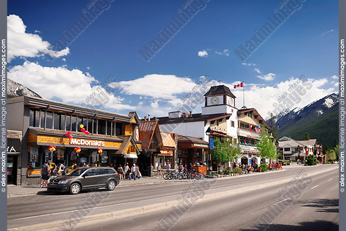 Street scenery of McDonald's and other shops and restaurants on Banff Avenue, downtown of Banff in Alberta Rockies with Rocky Mountains in the background. Alberta, Canada 2017