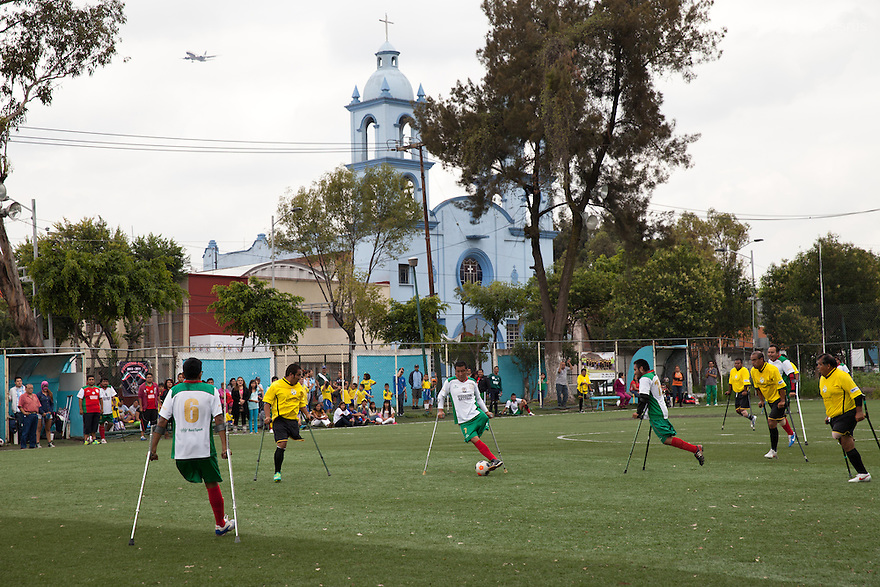 "Salvador Avendaño Vasquez, a player from Guerreros Aztecas, controls the ball during a soccer game with Los Dragones (""the Dragons"") in Mexico City, Mexico on July 5, 2014. Salvador Avendaño Vasquez, 25, lost his left leg in a car accident in may 2010. He joined the team in 2012. Until his accident, he sold fruit and vegetables. He now runs a street stall. Guerreros Aztecas (""Aztec Warriors"") is Mexico City's first amputee football team. Founded in July 2013 by five volunteers, they now have 23 players, seven of them have made the national team's shortlist to represent Mexico at this year's Amputee Soccer World Cup in Sinaloa this December. The team trains twice a week for weekend games with other teams. No prostheses are used, so field players missing a lower extremity can only play using crutches. Those missing an upper extremity play as goalkeepers. The teams play six per side with unlimited substitutions. Each half lasts 25 minutes. The causes of the amputations range from accidents to medical interventions – none of which have stopped the Guerreros Aztecas from continuing to play. The players' age, backgrounds and professions cover the full sweep of Mexican society, and they are united by the will to keep their heads held high in a country where discrimination against the disabled remains widespread. (Photo by Bénédicte Desrus)"