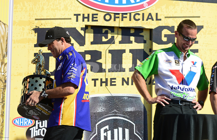 Nov. 11, 2012; Pomona, CA, USA: NHRA funny car driver Ron Capps (left) walks off with the championship trophy while Jack Beckman looks on during the Auto Club Finals at at Auto Club Raceway at Pomona. Mandatory Credit: Mark J. Rebilas-