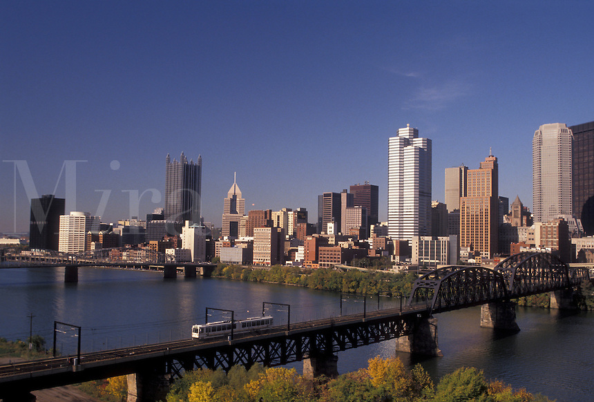 AJ3188, Pittsburgh, skyline, Pennsylvania, A scenic view of the downtown skyline of Pittsburgh from across the Monongahela River in the state of Pennsylvania. A public train crosses a bridge over the river heading away from the city.