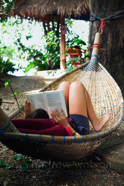 A tourist reads a book whilst relaxing in a woven rattan hammock.  Nong Khai, Nong Khai Province, THAILAND.