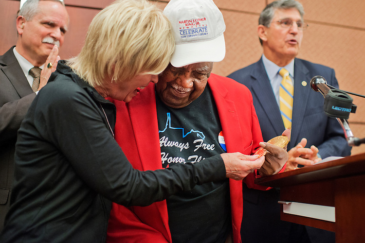 UNITED STATES - MAY 20: Sgt. John M. Watson, 96, of Beckley, W.Va., gets a hug from Dreama Denver, of Always Free Honor Flight during a luncheon in the Capitol Visitor Center where Watson received a Congressional Gold Medal and was recognized by the Tuskegee Airmen Association, May 20, 2015. Rep. David McKinley, R-W.Va., left, and Sen. Joe Manchin, D-W.Va., are also pictured. (Photo By Tom Williams/CQ Roll Call)