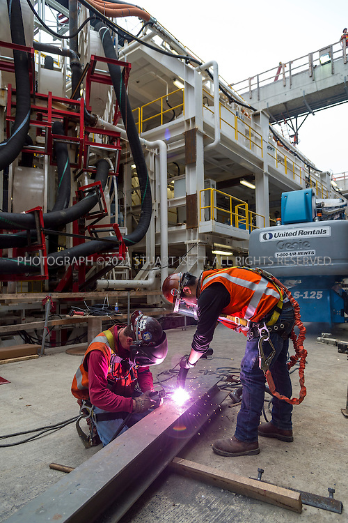 7/20/2013--Seattle, WA, USA<br /> <br /> &quot;Big Bertha&quot;, the massive deep bore tunneling machine, will soon start escalating under Seattle building a 1.7 mile tunnel to replace the aging Alaskan Way Viaduct on Highway 99. The drill is the largest ever built and when finished with allow 4 lanes of traffic to bypass downtown Seattle.<br /> <br /> Here, workers with Seattle Tunnel Partners, do some last minute work before the machines starts boring it's way under Seattle.<br /> <br /> The $80 million dollar machine was built in Japan by Hitachi-Zosen and is 57 feet, 4 inches in diameter and 322 feet long.<br /> <br /> WSDOT plans to complete the $2 billion tunnel by late 2015 with funding from gas taxes and later, tolls.<br /> <br /> <br /> &copy;2013 Stuart Isett. All rights reserved.