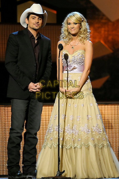 BRAD PAISLEY & CARRIE UNDERWOOD .43rd Annual CMA Awards, Country Music's Biggest Night, held at the Sommet Center, Nashville, Tennessee, USA, 11th November 2009. .live show on stage .full length cowboy hat black suit strapless yellow dress gown long maxi embroidered flowers .CAP/ADM/LF.©Laura Farr/AdMedia/Capital Pictures.
