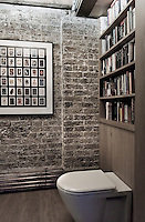 Brick walls, copper pipes and natural wood, combined with a framed collection of playing cards and a toilet with integrated bookshelves, enhance the eclectic domestication of this old industrial building