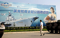 A man walks past a billboard featuring Soviet aircraft carrier Kiev in a military-theme park in Tianjin, China. 19 Aug 2007
