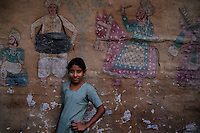 A girl standing in front of a painted wall at Katputly colony in New Delhi, India. 15.11.2009. Kathputly colony is a slum area in West Delhi. This slum seems like any other slum areas of modern India with dysfunctional electricity, non existing sanitation and poverty. As a part of Delhi, this is also ailed with water crisis. Large families live their lives crammed together in a single room with all the odds which complement poverty. One thing which differentiates this slum with any other is the people living in the colony. Nearly everybody in this slum is a traditional performing artist; and they have been migrating to this area for last 50 years from different parts of the country for a better livelihood. They are magicians, acrobats, jugglers, puppeteers, dancers and musicians. These artistes perform in star rated hotels, marriage ceremonies of the richer section, functions, and festivities all around the country and the world. Most of the artisans I met here, have performed in Europe and America but such opportunities are rare to come by. They struggle to keep their art form alive. They say that they don't get any help or support from the government for their basic needs and for the well being of the Kathputly colony -  though they have uphold the prestige of the country internationally. Polluted air, dirty alleys smelling of urine, colourful dress and sound of music characterise Kathputly colony, which is the one of its kind in India. Arindam Mukherjee