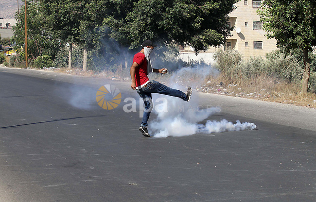A Palestinian protester kicks a tear gas canister fired by Israeli troops during clashes following a protest in solidarity with Palestinian prisoners held in Israeli jails, at the Hawara checkpoint near the West Bank city of Nablus on Aug. 18, 2016. Photo by Nedal Eshtayah