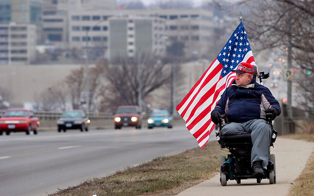 """What better way is there to honor the flag than to have it with you all the time?"" says Duncan Brayden of Des Moines west, as he travels along East University Avenue to visit a friend Monday, January 16, 2006.  Brayden, a U.S. Navy veteran who served during the Vietnam War aboard the USS Forrestal, says he rarely ever removes the American flag from his wheelchair.  He says it serves a dual purpose - to display his patriotism and to help motorists see him as he travels along busy roadways."