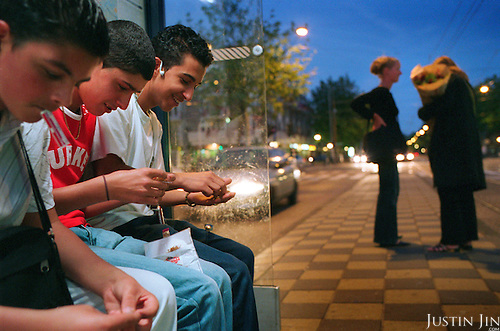 Dutch-Turkish teenagers roll marijuana  joints at a tram stop in Amsterdam. .Picture shot in Amsterdam in 2004 by Justin Jin. .