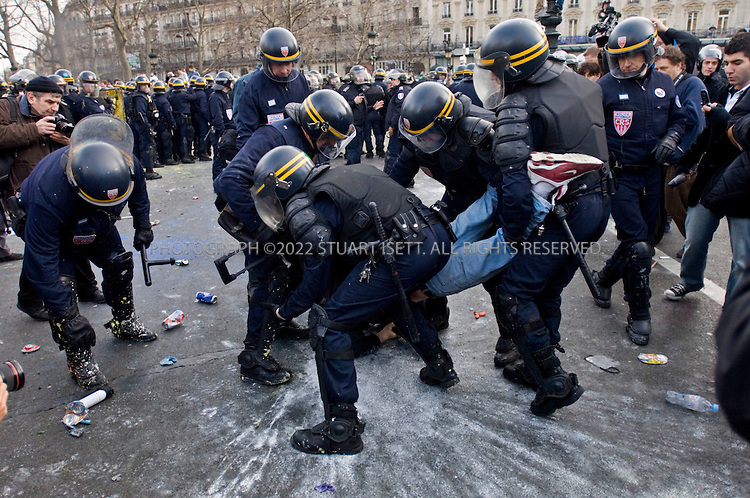3/28/2006--Paris, France..French riot police apprehend a protester during clashes at the end of a student and union protest against youth job law First Job Contract (CPE) in Paris March 28, 2006...A nationwide protest and general strike held today in France, by students and unions demanding the government scrap a new youth jobs law. Students and unions in France on Tuesday step up protests against the First Employment Contract (CPE) law, an open-ended contract for under 26 year-olds that can be terminated within the first two years without explanation...Photograph By Stuart Isett.All photographs ©2006 Stuart Isett.All rights reserved.