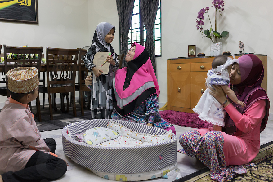 """January 15, 2015 - Rawang (Malaysia). Global Ikhwan CEO's first wife Saiyidah Lokman (center), fourth wife Mardiona Hakim (right) and 3 of their 27 children at the family home. Although polygamy is legal in Malaysia, it is rarely practiced in the open or with the knowledge and approval of all the wives involved in such a relationship. However,one companyin the country -Global Ikhwan - only employs women, who view polygamy as the integral element of """"the Islamic way of life."""" © Thomas Cristofoletti / Ruom"""