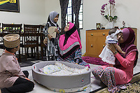 "January 15, 2015 - Rawang (Malaysia). Global Ikhwan CEO's first wife Saiyidah Lokman (center), fourth wife Mardiona Hakim (right) and 3 of their 27 children at the family home. Although polygamy is legal in Malaysia, it is rarely practiced in the open or with the knowledge and approval of all the wives involved in such a relationship. However, one company in the country - Global Ikhwan - only employs women, who view polygamy as the integral element of ""the Islamic way of life."" © Thomas Cristofoletti / Ruom"