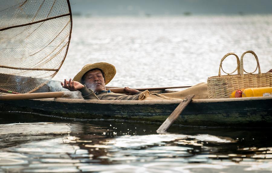 INLE LAKE, MYANMAR - CIRCA DECEMBER 2013: Fisherman taking a rest and smoking in his boat in Inle Lake, Myanmar