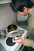 University student cooking a meal in student accommodation kitchen,