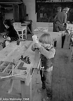 A.S.Neill, wearing flat cap, in the background, carpentry workshop, Summerhill school, Leiston, Suffolk, UK. 1968.