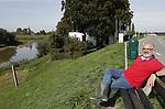 Foto: VidiPhoto<br /> <br /> DODEWAARD &ndash; Ruim 400 jaar natuur- en oorlogsgeweld heeft de -naar eigen zeggen- oudste herberg (De Engel) overleefd. Een of meerdere bevers langs de dijk bij Dodewaard dreigen nu de historische horecagelegenheid ernstig te ondermijnen. Frappant genoeg werd tijdens het maken van deze reportage een vierde hol ontdekt, net onder het waterpeil van de historisch lage strang langs de dijk. Waar nu de strang meandert, stroomde eeuwen geleden de Waal. Enkele jaren geleden werden er in de uiterwaarden van Dodewaard bevers uitgezet, beschermde dieren waar je alleen maar naar mag kijken. Een prachtig gezicht als ze voorbij komen zwemmen op hun rug, vertelt eigenaar Inno Venhorst van De Engel maandag. Tijdens het hoge water van afgelopen winter zochten de dieren het echter hogerop en groeven enkele gangen in het talud van de waterkering voor de herberg. Waar die gang ophoudt is nog niet duidelijk, maar de kans is groot dat een bever bij nieuw hoog water zijn kop omhoog steekt op het terras, achter de waterkering. Bevers graven namelijk schuin omhoog. Met als gevolg dat De Engel onder water komt te staan. En drie maanden water in het pand betekent een faillissement. Maar niet alleen het restaurant van Venhorst, ook de dijk wordt bedreigd. Onder de wijngaard naast de herberg en voor de dijk, bevinden zich meerdere gangen. De grootste daarvan veroorzaakte vlak voor de druivenoogst een lelijk ongeval toen de restauranthouder er met zijn tractor wegzakte en vervolgens om sloeg.