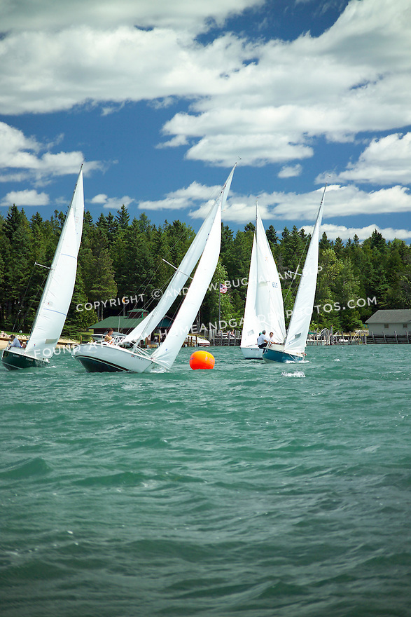 Four ensign-class sailboats, their white sails filled with wind, sail towards the camera and prepare to round a large orange marker buoy in this on-the-water photo, while a blue sky with white clouds above and a close-in evergreen-lined shore help set the scene for this summer image.