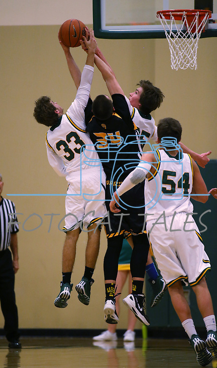 Manogue's Jack Sanders and Justin DeGeus fight for a loose ball with Galena's Zack Lessinger at Manogue High School in Reno, Nev., on Tuesday, Feb. 11, 2014. Manogue won 51-29.<br /> Photo by Cathleen Allison