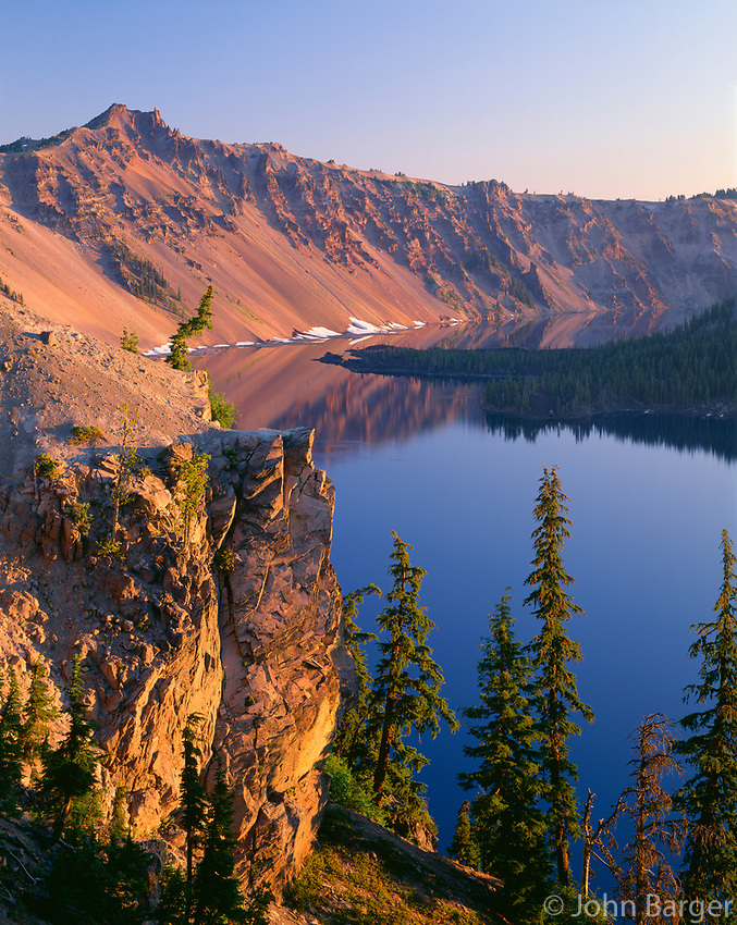 USA, Oregon, Crater Lake National Park, Sunrise glow on west rim of Crater Lake with Hillman Peak (left) overlooking Wizard Island.