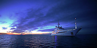 Pegaso rides at anchor against a spectacular evening sky