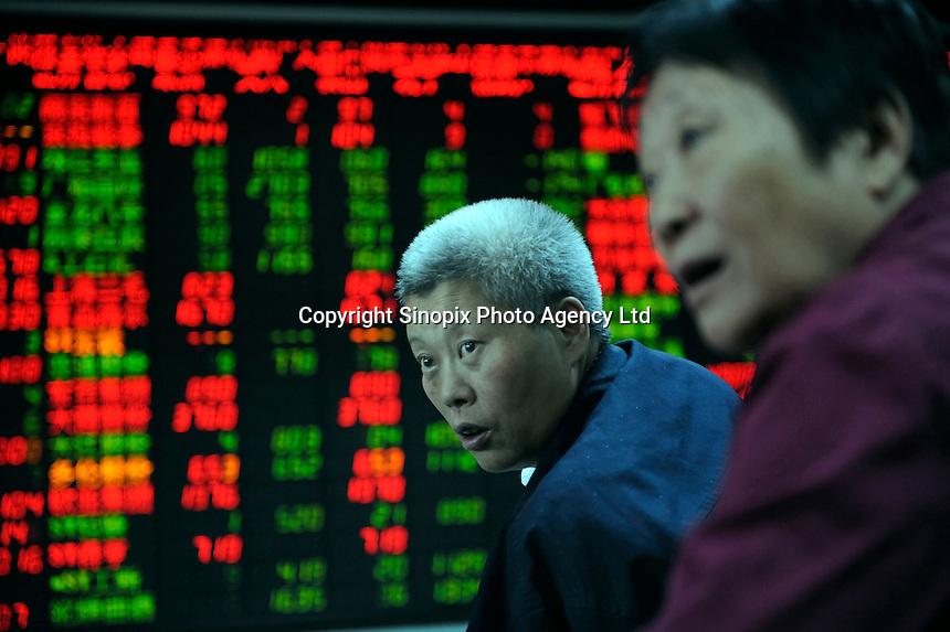 Investor look at stock index quotes at a securities firm in Beijing, China..21 Sep 2009