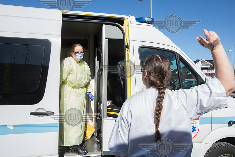 Paramedic in the city of Drammen wearing personal protective equipment (PPE) in order to transport patients during the Covid-19 , coronaviraus, pandemic. A nurse at an institution directs the ambulance to a separate entrance. <br /> <br /> <br /> ©Fredrik Naumann/Felix Features