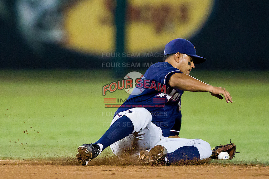 Christian Colon (4) of the Northwest Arkansas Naturals makes a stop on a hard hit ball to short during a game against the Springfield Cardinals at Hammons Field on July 31, 2011 in Springfield, Missouri. Northwest Arkansas defeated Springfield 9-1. (David Welker / Four Seam Images)