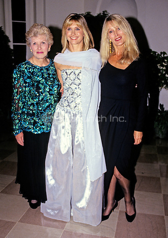 Australian singer, songwriter and actress Olivia Newton-John, center, arrives for the State Dinner hosted by United States President George H.W. Bush and first lady Barbara Bush honoring President V&middot;clav Havel of Czechoslovakia at the White House in Washington, DC with her mother, Irene Newton-John, left, and sister, Rona Newton-John, right, on October 22, 1991.<br /> Credit: Ron Sachs / CNP/MediaPunch