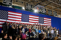 People watch as US President Barack Obama delivers a speech at the Central High School gymnasium in Manchester, New Hampshire, on Tuesday, Nov. 22, 2011.  During the speech, Obama directly challenged Congress on the economy and spoke about the American Jobs Act, a law he stresses as necessary to ease taxes for ordinary Americans and promote job growth.  The speech was interrupted briefly by Occupy protesters who were quickly drowned out by supporters.