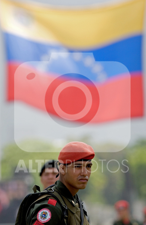 A Venezuelan presidential guard soldier with the Venezuelan flag in background, watches a military parade in Caracas, Venezuela, on Wednesday, Jul. 05, 2006. The military parade was to celebrate the 195th anniversary of the Venezuelan Independence from Spain. (ALTERPHOTOS/Alvaro Hernandez)