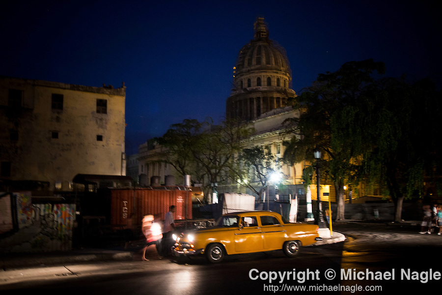 HAVANA, CUBA -- MARCH 23, 2015:  People walk near the National Capital Building at dusk in Havana, Cuba on March 23, 2015. Photograph by Michael Nagle