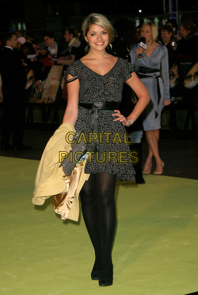 "HOLLY WILLOUGHBY.Arrivals at the Warner Bros. World Premiere of ""Alien Autopsy"" held at the Odeon Cinema, Leicester Square, Londn, England, April 3rd 2006..full length black and white patterned dress hand on hip holding coat bag tights strap falling down polka dot belt.Ref: AH.www.capitalpictures.com.sales@capitalpictures.com.©Adam Houghton/Capital Pictures."