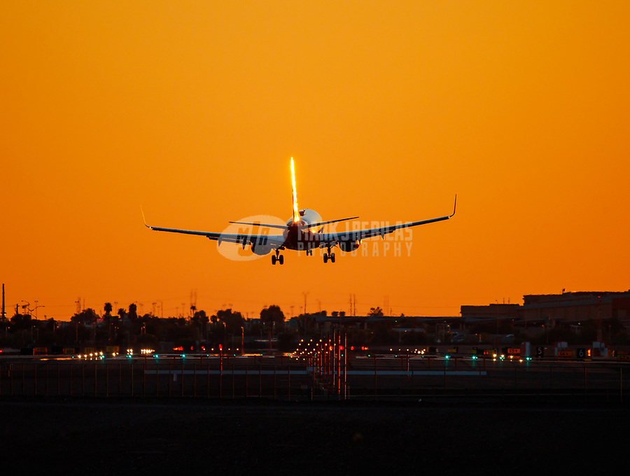 Aug 8, 2017; Phoenix, Arizona, USA;   A Southwest Airlines jet is silhouetted as it lands at Phoenix Sky Harbor International Airport. Mandatory Credit: Mark J. Rebilas