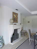 A painting in an antique frame hangs above the pale stone fireplace in the dining room