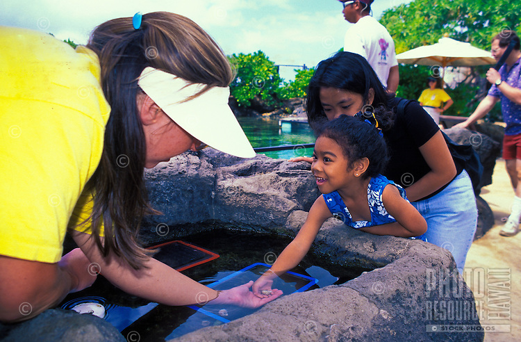 A young girl explores some unique sea creatures at the Edge of the Reef tank  at the Waikiki Aquarium.